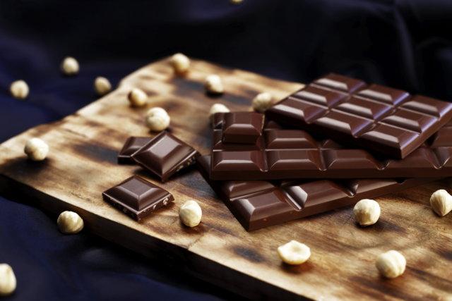 Vue de tablettes et de carrés de chocolat noir et de noisettes entières posés sur une planche en bois.