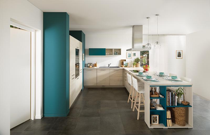 Vue latérale d'ensemble de la cuisine Arcos, coloris gris clair Slow Wood, avec l'évier et la crédence suspendue en arrière plan, une table et des chaises hautes au premier plan.