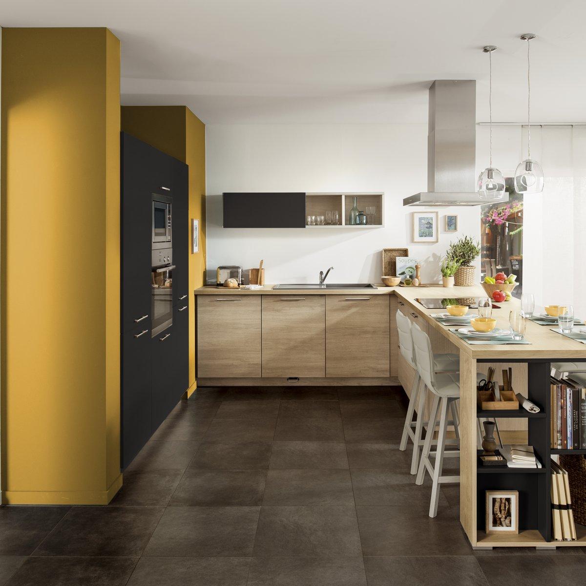 Le bois Vintage Oak de cette cuisine se marie parfaitement au mur jaune moutarde.