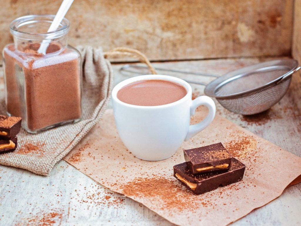 Vue d'une tasse de chocolat chaud posée sur une table avec un pot de chocolat en poudre et des carrés de chocolat.