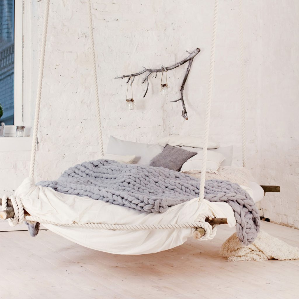 Vue d'un lit fait façon « balançoire » de style campagne fait de bois massif, décoré avec des draps et des couettes beige et gris et accroché au plafond par des cordes blanches.