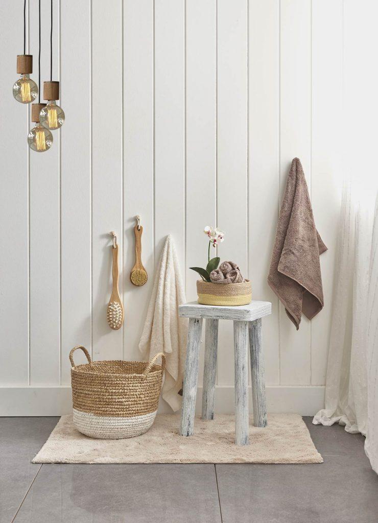 Vue d'un ensemble d'accessoires pour la salle de bains (tabouret, panier, brosses, serviettes, tapis de bains) posés devant un mur de bois lambrissé peint en blanc.