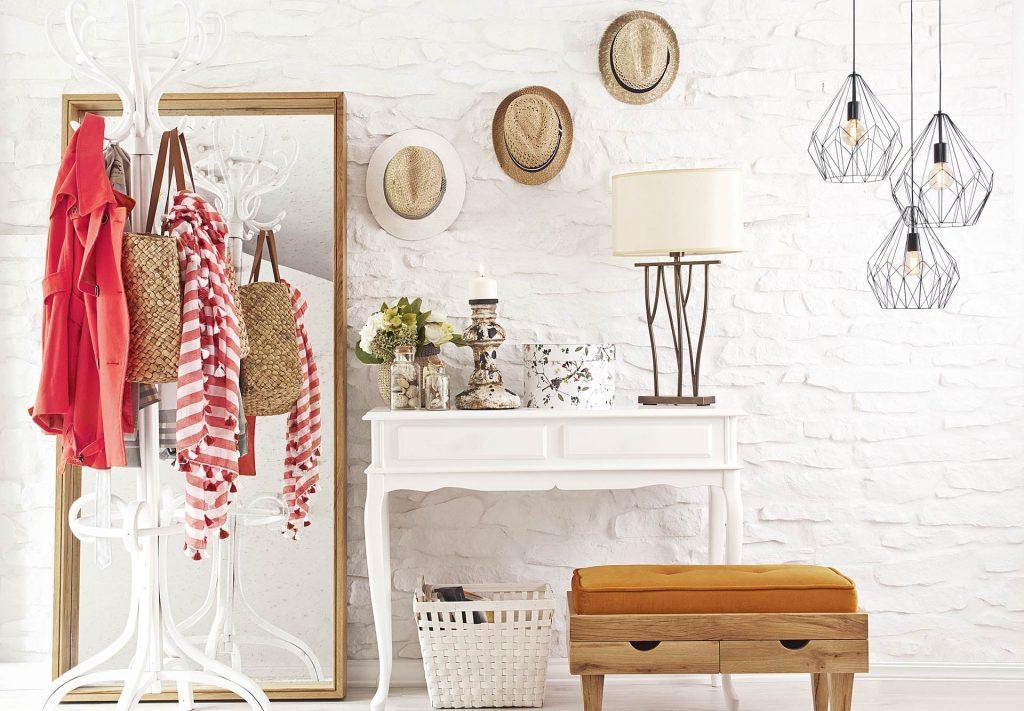 Vue d'une console blanche à côté d'un miroir, avec un porte-manteaux chargé de vêtements et avec des lampes de style atelier en fil métallique noir.