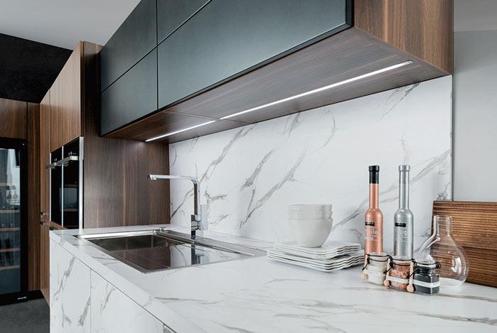 Vue zoomée de la cuisine Arcos Edition avec le plan de travail effet marbre et de l'éclairage dans le meuble haut.