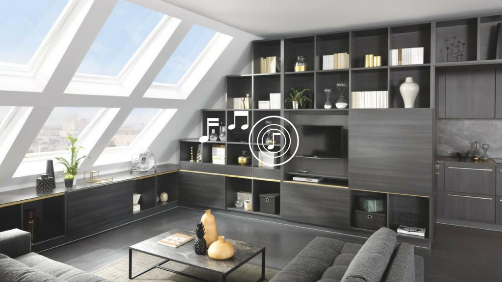 Vue de biais de la sous pente avec la bibliothèque et la cuisine Arcos coloris noir effet bois Zonza dans le fond à droite.