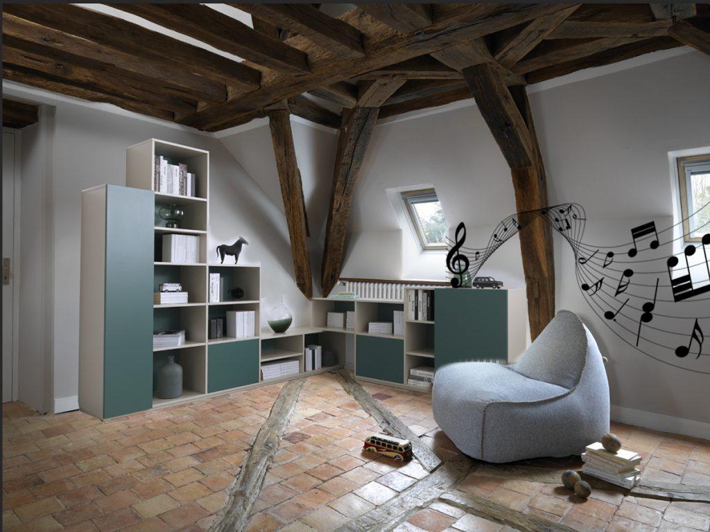 Vue d'ensemble de la bibliothèque d'angle Loft, coloris vert Shamrock et grège clair Kashmir Grey, avec l'armoire en avant plan, la colonne d'étagères, des blocs coulissants surplombée de niches ouvertes assemblées dans l'angle et un meuble bas avec portes battantes.