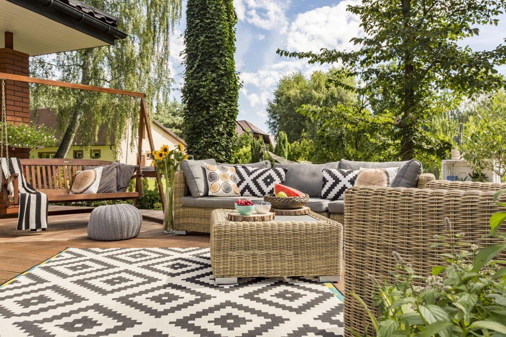 Terrasse avec du mobilier de jardin (fauteuil, canapé, table basse, banc) et de la décoration à motifs géométriques en noir et blanc (tapis et coussins).