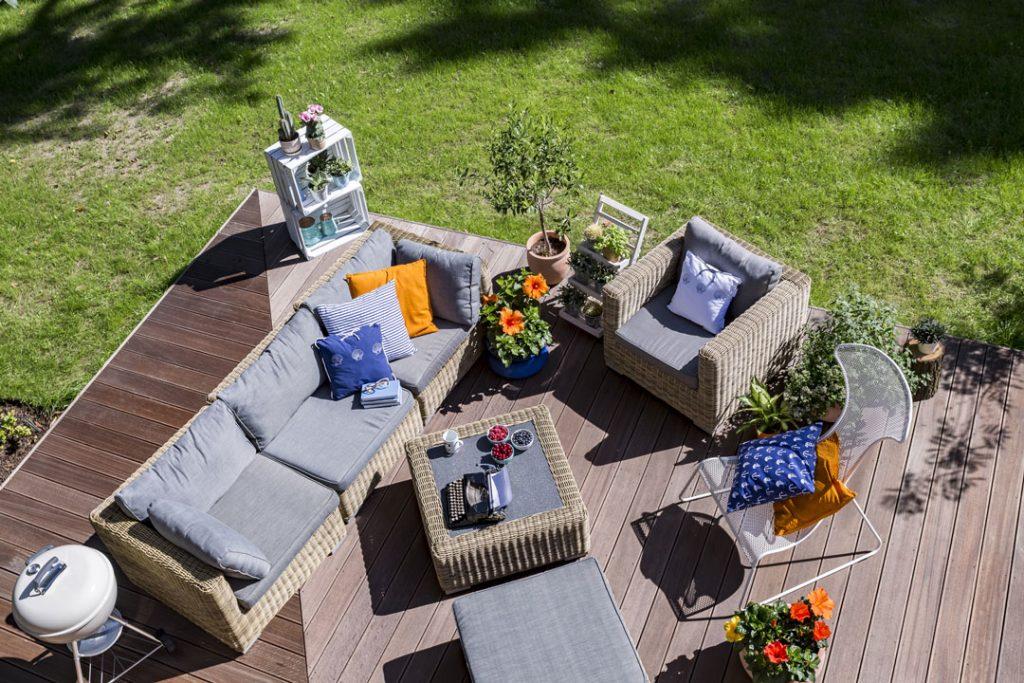 Mobilier de jardin esprit salon (fauteuil, canapé, table basse, chaise, pouf) coloris gris et décoration en bleu et jaune moutarde, sur une plate-forme en bois.