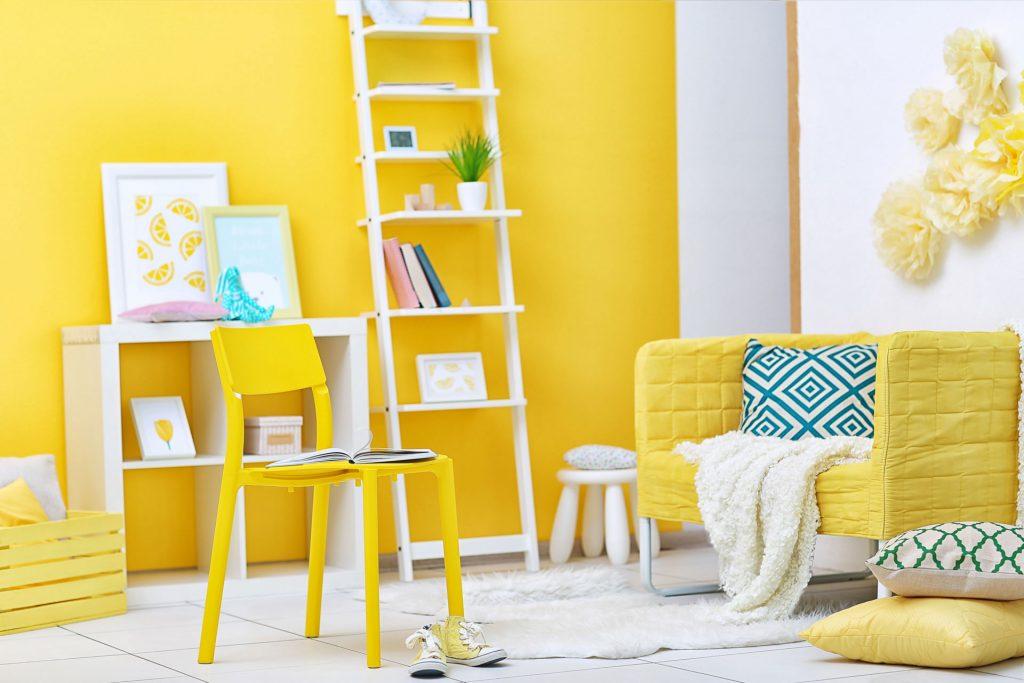 Chambre avec un mur jaune, deux étagères blanches, une chaise et un fauteuil jaunes et des éléments de décoration en bleu, jaune et blanc.