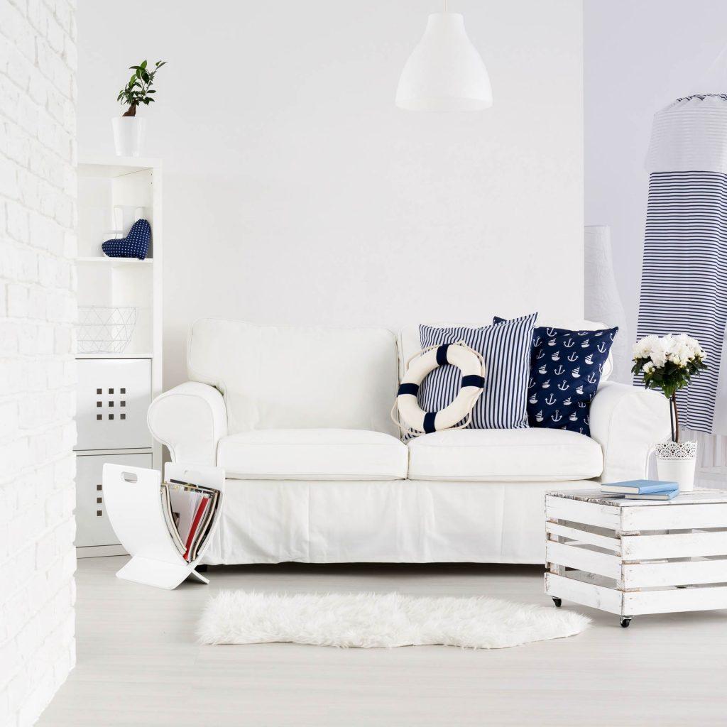Chambre blanche, ambiance navy avec un canapé blanc décoré avec deux coussins bleu marine et une bouée.