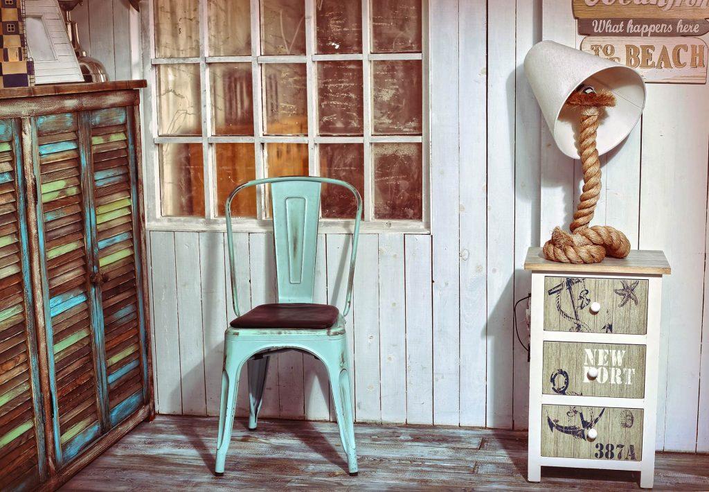 Décoration style plage avec une chaise en métal en bleu, deux meubles vintage et une lampe avec un nœud de corde comme pied.