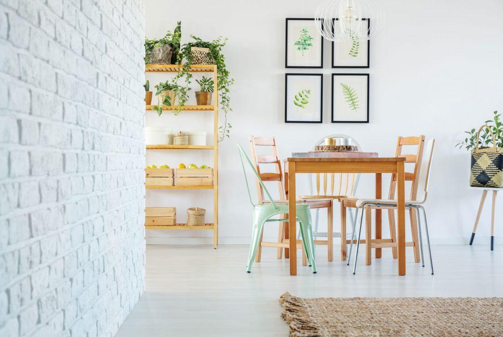 Étagère en bois naturel décorée avec des plantes vertes et des boîtes en bois à côté d'une table avec des chaises en métal et en bois, et quatre tableaux à motifs végétales derrière.
