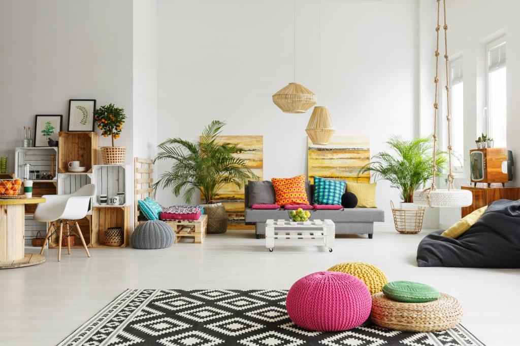 Chambre décorée avec des couleurs vives et acidulées, avec des poufs, un tapis à motifs géométriques, des meubles en palette et des plantes vertes.