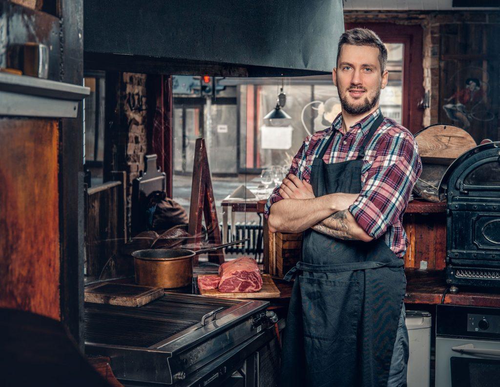 Vue d'une cuisine avec une grille, un four et d'autres ustensiles de cuisine, et un homme qui pose à côté d'une planche en bois sur laquelle il y a un morceau de viande.
