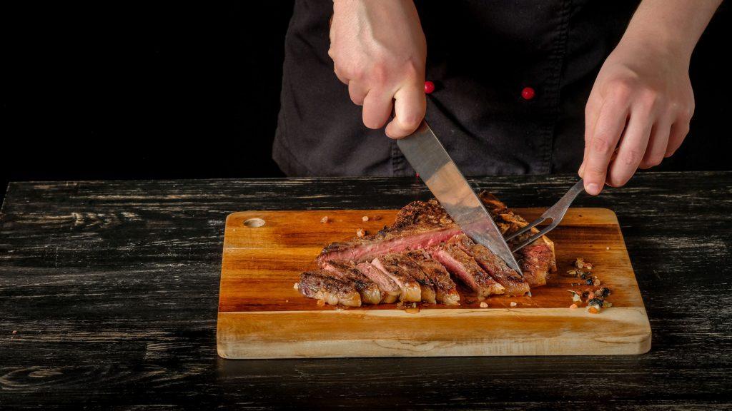 Gros plan sur une planche en bois sur laquelle on voit les mains d'un chef en train de couper un steak cuit.