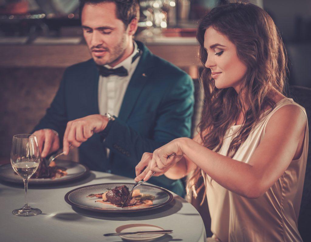 Un homme et une femme bien habillés qui mangent un plat de viande et boivent du vin blanc.