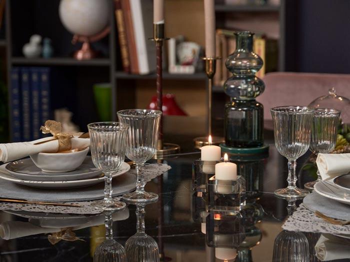 vue de détaille d'une table en céramique avec des assiettes et bougies esprit lagom et hygge
