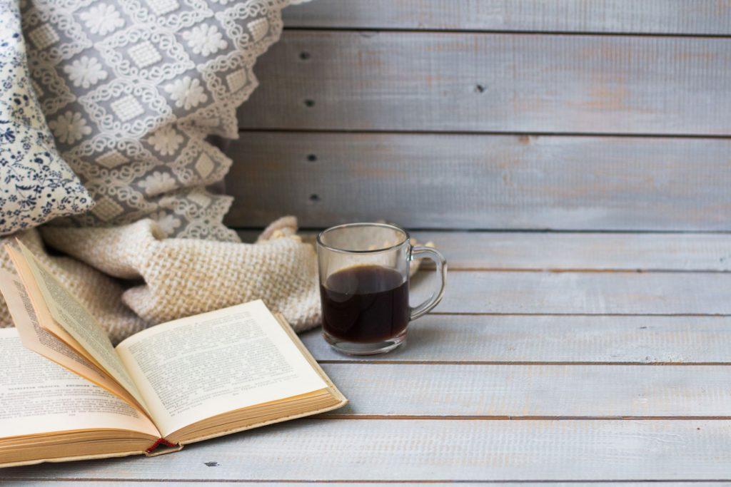 Vue détaillée d'un banc en bois gris avec un livre, une tasse de café, des coussins déco et un plaid placés dessus.