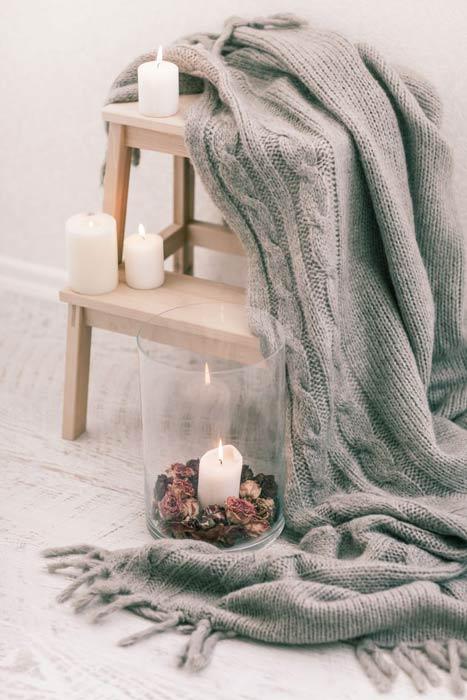 Noël hygge lagom : Vue d'un plaid gris placé sur une petite marche en bois clair décorée de bougies.