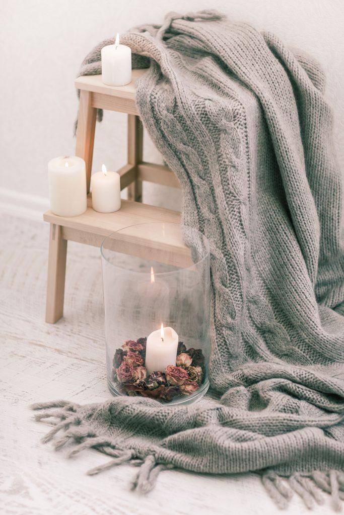 Vue d'un plaid gris placé sur une petite marche en bois clair décorée de bougies.