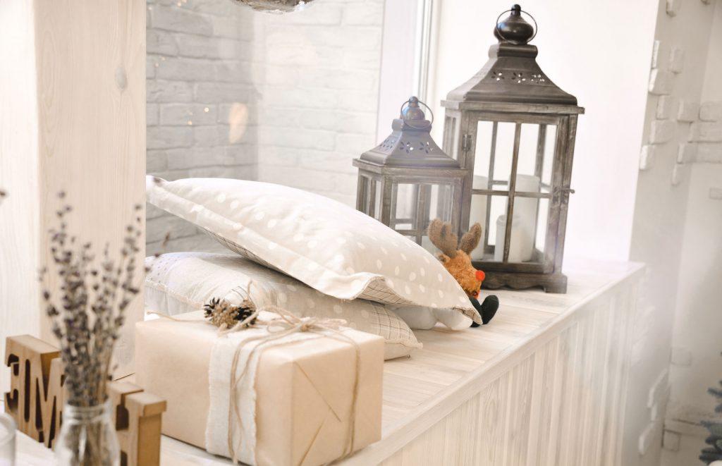Vue détaillée d'une fenêtre blanche sur laquelle il y a des coussins gris et blancs, des lanternes grises et une boîte emballée de papier beige.