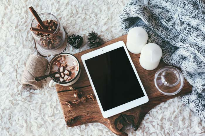 Vue d'une tablette numérique posée sur une planche en bois avec une tasse de chocolat et un pot d'épices, des bougies, une couverture en mailles et une pelote de ficelle, sur une couverture blanche.
