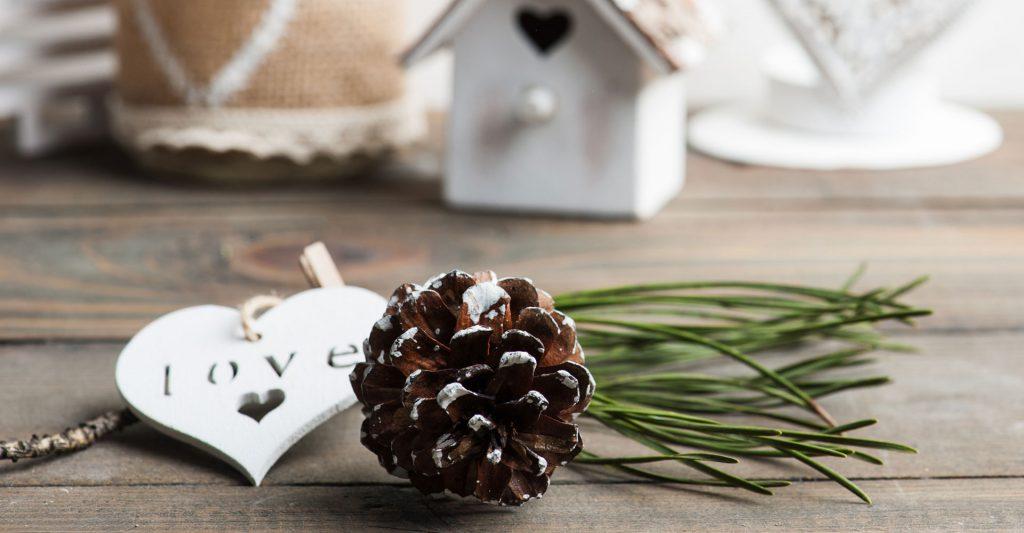 Vue d'accessoires décoratifs variés de couleur blanche et beige arrangés derrière une pomme de pin et un brin d'épicéa.