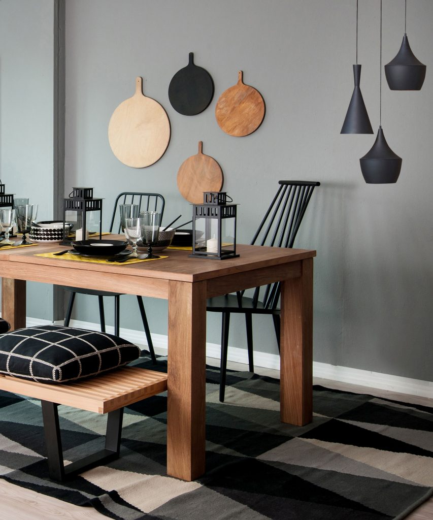 Vue d'une table en bois posée sur un tapis à motifs graphiques noir, gris et blanc avec des sièges noir et bois et des lampes suspendues noir mat.