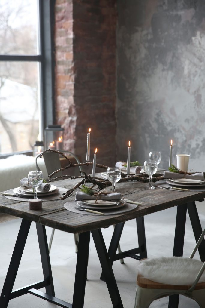 Vue d'une pièce de style campagnard avec une table en bois foncé et des chaises préparée pour un dîner romantique avec des bougies et des verres à vin au premier plan et un mur en briques et en béton gris en arrière plan.