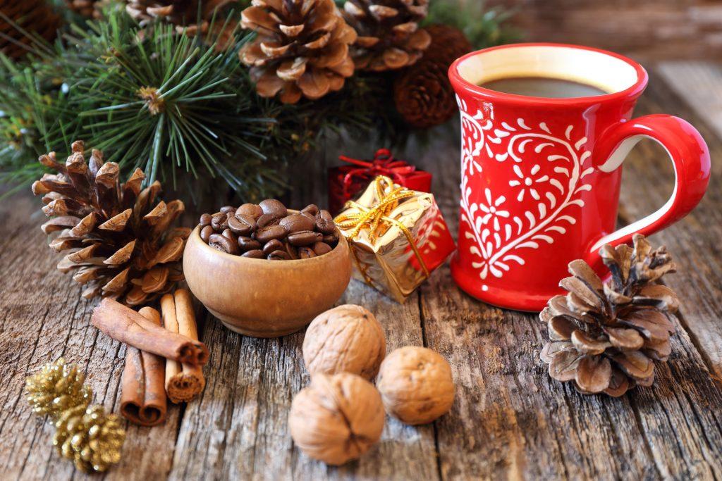 Vue d'une tasse avec un décor façon Noël mise en valeur sur du bois avec un décor de pommes de pin, branches d'épicéa et épices (café, cannelle, noix).