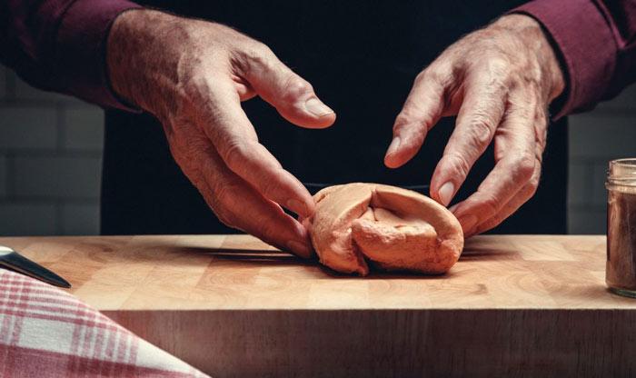 Deux mains d'homme en train de commencer à préparer un foie gras cru entier posé sur une planche en bois.