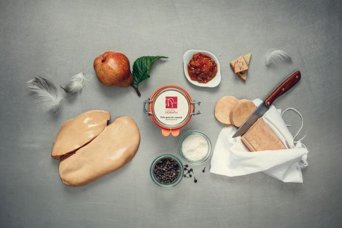 Un bocal de foie gras Lucien Doriath, un foie gras cru entier et un foie gras entier cuit posé sur son torchon et coupé avec un couteau, placés sur une surface avec un pot chutney, un de sel et un de poivre, et d'autres éléments de décoration (plumes, poire).