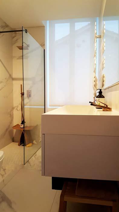 Vue de biais de la salle de bains de Jo Yana, avec la douche à l'italienne en arrière plan et le lavabo au premier plan et le marbre aux murs et au sol.