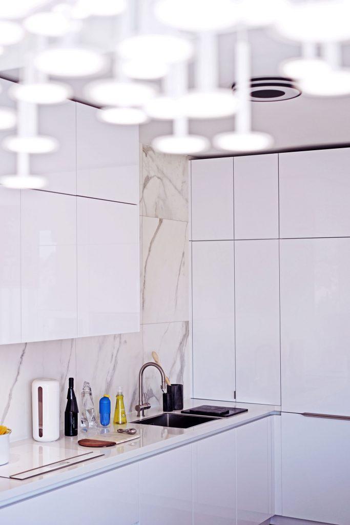 Vue de biais du plan de travail blanc avec cuve sous plan de la cuisine de Jo Yana et des meubles pour le rangement sur mesure de 3 mètres.