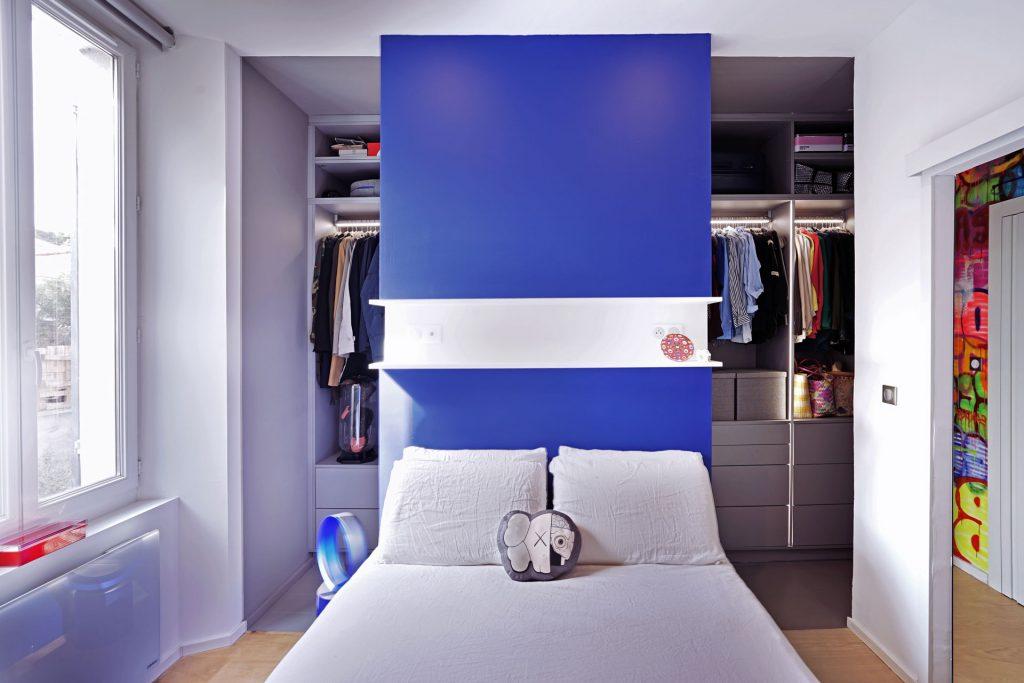 Vue du dressing de Jo Yana en arrière plan, caché en partie par le lit avec un mur bleu comme tête de lit au milieu.
