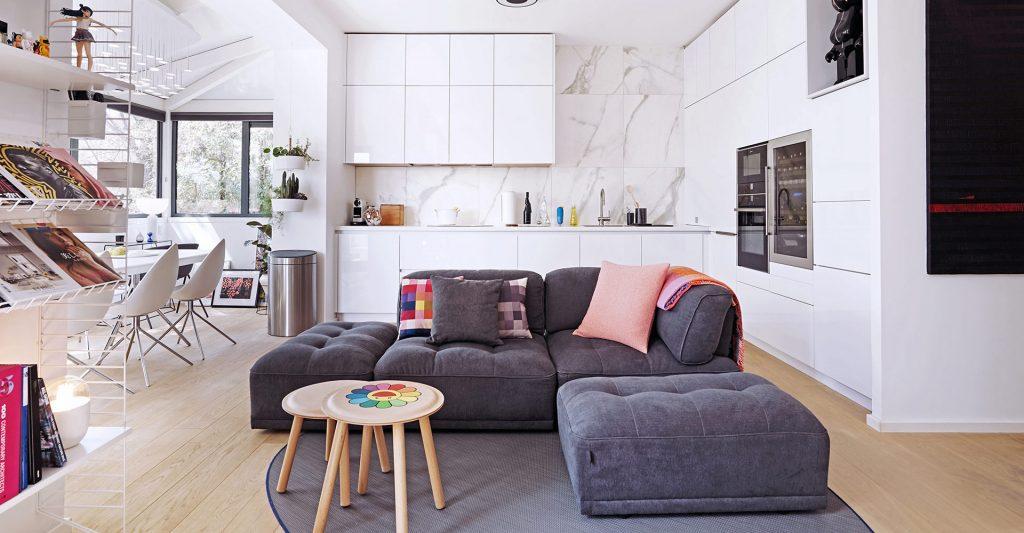 Vue de face du canapé gris, décoré avec plusieurs coussins et une couverture pliée, de la pièce à vivre de Jo Yana, avec la cuisine blanche en L et la table à manger en arrière plan.