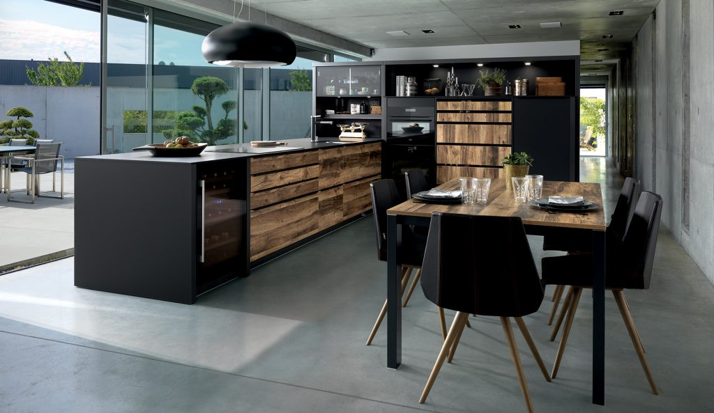 Vue d'ensemble de la cuisine design Arcos Edition avec les façades couleur marron clair effet bois et le plan de travail stratifié fin noir.