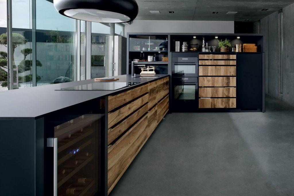 Vue du linéaire qui souligne la finesse du plan de travail compact couleur noire Nano Black dans la cuisine Arcos Edition, façades coloris marron clair effet bois Murphy.