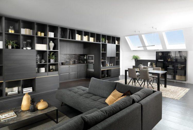 Vue de biais de la cuisine ouverte Arcos, coloris noir effet bois, avec une fenêtre sur la sous pente, une table et des chaises dans le fond et le salon en premier plan.