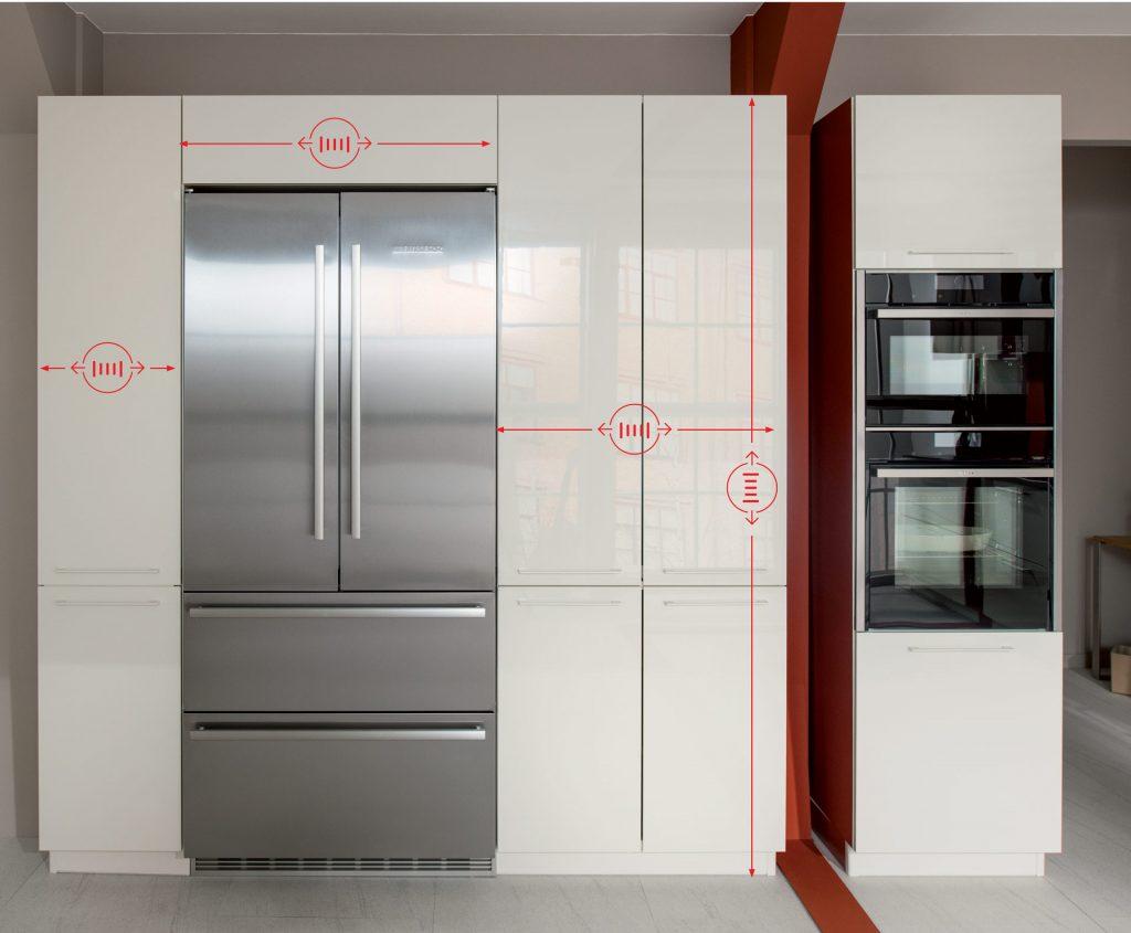 Vue de détail d'un meuble de rangement de cuisine Strass coloris beige, portes fermées, avec flèches indicatives pour le sur-mesure en hauteur et en largeur.