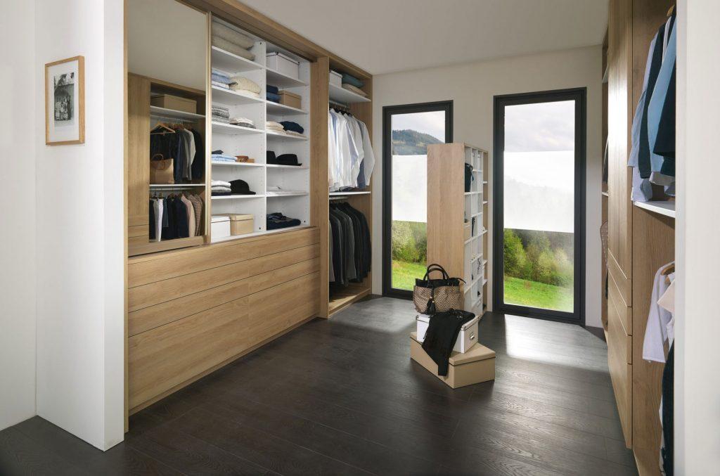 Vue de biais du dressing Arcos, coloris bois, avec la porte coulissante miroir du côté droit du placard.