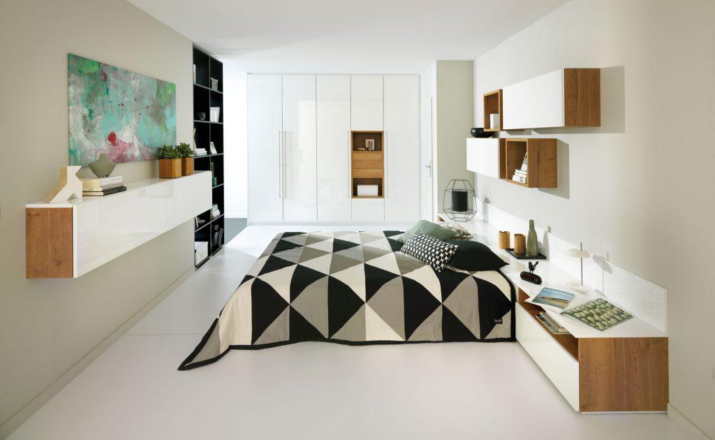 Vue d'ensemble d'une chambre de style contemporain, avec le lit et ses meubles au premier plan, le placard dressing en arrière plan, un meuble suspendu sur la gauche, et des caissons sur la droite, tous dans les coloris blanc et décor bois.
