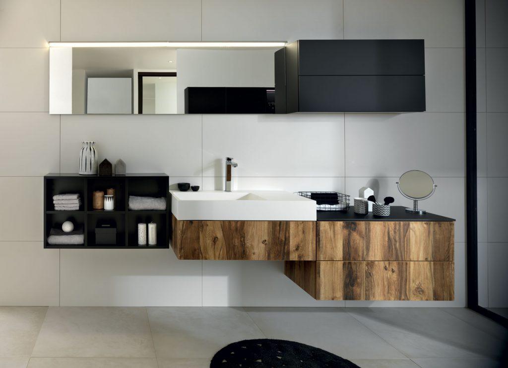 Vue de face de la vasque et du plan de toilette face au miroir de la salle de bains Arcos Edition, coloris marron clair effet bois et noir.