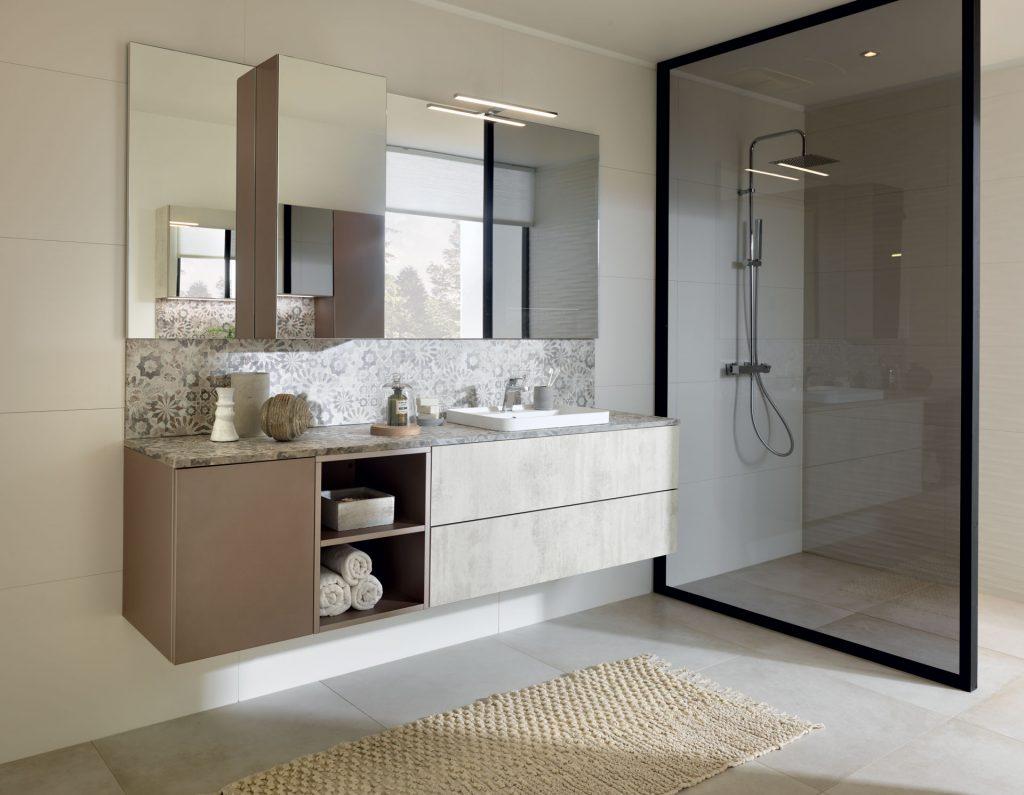 Vue de biais de la salle de bains Arcos Edition coloris gris clair marbré Marvel light et Loft coloris marron clair cacao Iron Blush et la crédence avec le motif Mexico.