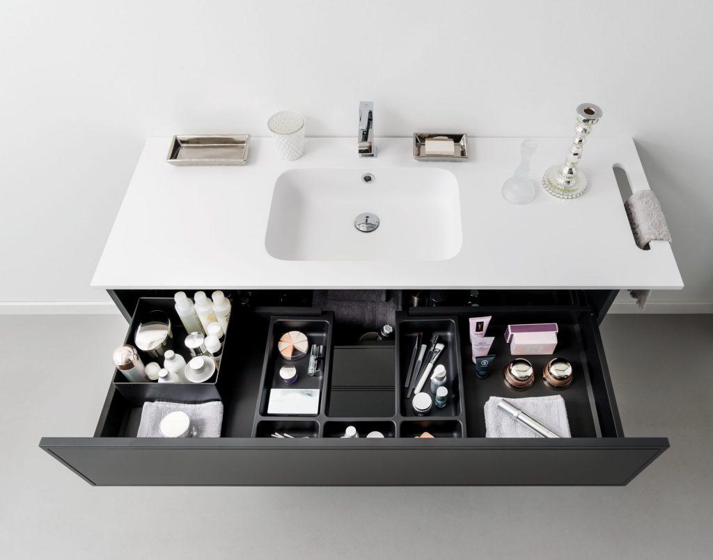 Vue de face du meuble bas sous vasque avec le bloc coulissant du haut ouvert et mis en situation avec des accessoires, modèle Boxea coloris gris foncé.
