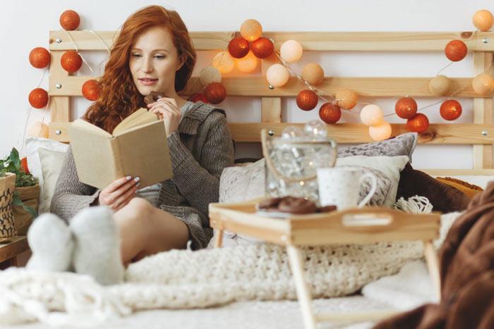 Noël hygge lagom : Une femme lit un livre sur son lit décoré avec des couvertures beiges et marron, des coussins, et une tête de lit en bois avec une guirlande lumineuse avec des boules oranges et beiges. Un plateau en bois avec du pain d'épices et une tasse est posé sur le lit.
