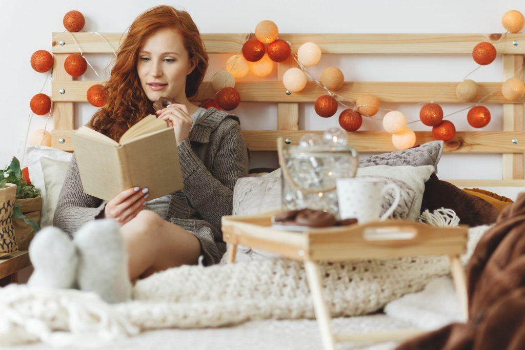 Une femme lit un livre sur son lit décoré avec des couvertures beiges et marron, des coussins, et une tête de lit en bois avec une guirlande lumineuse avec des boules oranges et beiges. Un plateau en bois avec du pain d'épices et une tasse est posé sur le lit.