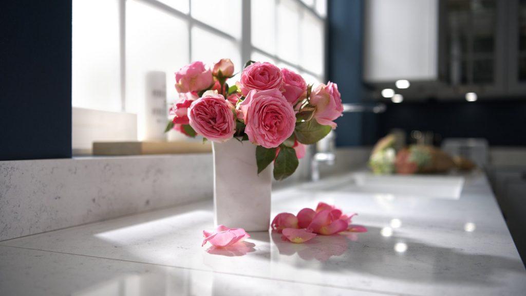 Un bouquet de roses dans un vase en céramique blanche et des pétales sur un plan de travail en quartz, orientation paysage.