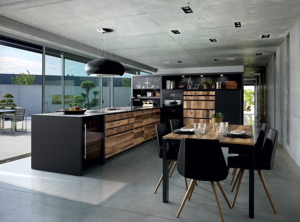 Vue d'ensemble de la cuisine Arcos Edition avec les façades couleur marron clair effet bois Murphy et le plan de travail fin coloris noir Nano Black.