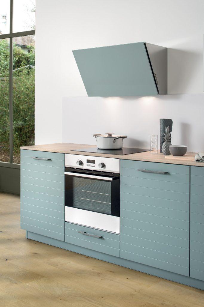 Vue de la zone de cuisson de la cuisine Multiway Arcos avec le bas four et la hotte laquée assortie aux coloris de la façade, vert clair grisé Green Tea.